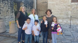 Dorothy Schultze, co-chair of Junior Associates Committee, Pam Rosser, Alamo Conservator, and Virginia Van Cleave, chair of Junior Associates committee stand with four Junior Associates and Emily Margaret during their visit to the Alamo!